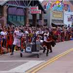 Photo of 4 people racing a coffin down Manitou avenue with a crowd